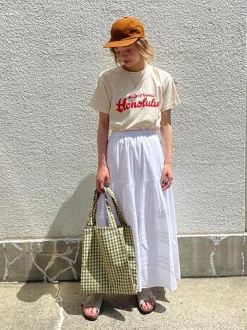 オレンジのキャップを主役にしたコーディネートも素敵♪Tシャツとロングスカートをワントーンでまとめることで、トレンド感のある着こなしに。
