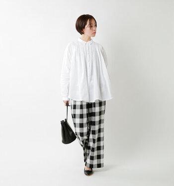 子供っぽくなりがちなチェック柄でも、白と黒の組み合わせで大人スタイルを作れます。ヘムラインがふわっと広がるチュニックブラウスを合わせることで、クールとフェミニンのバランスが絶妙な着こなしに。