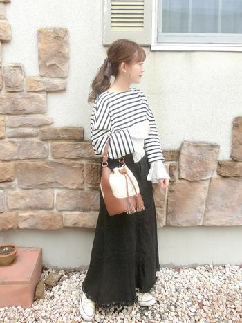 黒デニムロングスカートも、秋まで長く活躍してくれるアイテムです。デザイン性あるボーダーTに白スニーカーなどを合わせて、カジュアルでいてフェミニンな印象にまとめたいときに◎バッグのブラウンも季節感を演出してくれます。