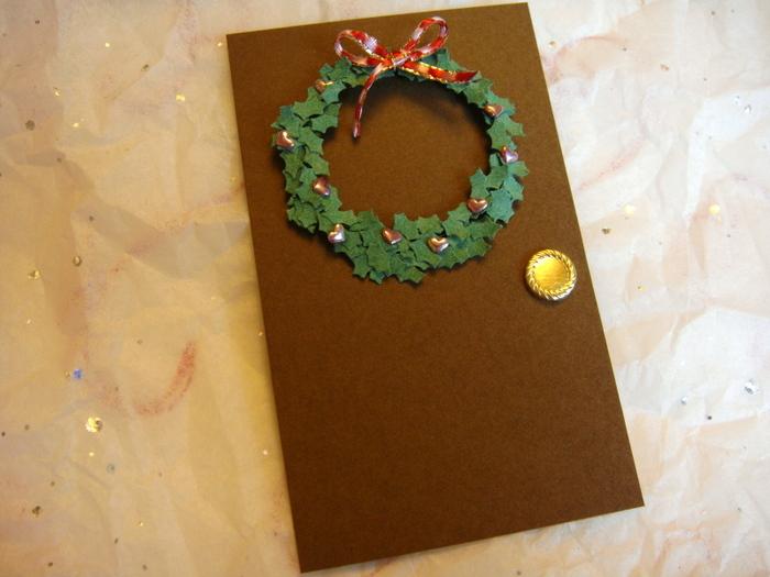 ドアにリースを掛けた、クリスマスの朝を思わせるような遊び心のあるメッセージカード。柊のクラフトパンチで切り抜いて丸く重ねて、リボンやビーズで飾り付け。メッセージカードは、二つ折りにした茶色の画用紙にボタンをつけてドアに見立てています。ちょっとした工夫で心掴まれるようなカードを作れますよ!