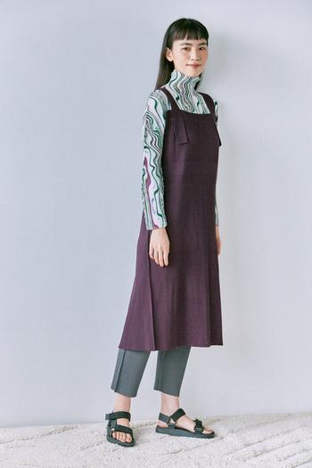 マーブル柄が描かれたハイネック長袖シャツ。遊び心のある存在感抜群のアイテムですが、レイヤードに一役買ってくれる優れもの。柄の紫と同じ色のエプロンワンピースを合わせて統一感のある着こなしに。