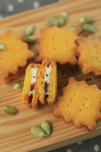 サクサク食感のかぼちゃクッキーでホワイトチョコを挟んだ、甘くて優しいスイーツです。刻んだクランベリーの酸味がアクセントになっています。かぼちゃはパウダーを使うので、生地にも混ぜやすいですよ♪