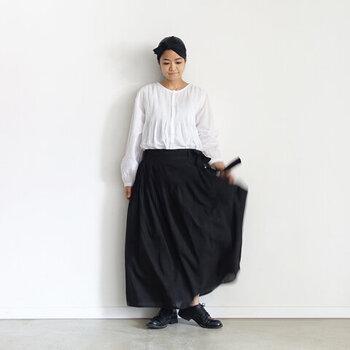 黒いスカートと合わせれば、きちんとした印象に。 ウエストインにすると上品に、アウトにすると抜け感が生まれます。