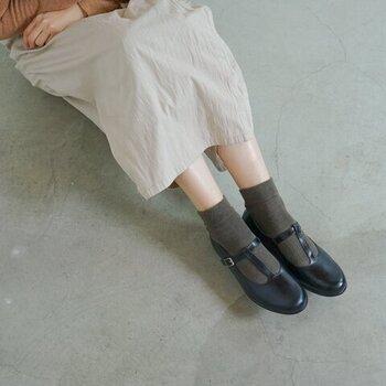 クラシカルなTストラップが女性らしい革靴はふんわりとしたスカートと合わせてより甘いスタイルに。カーキの靴下を覗かせれば、足元から秋の気配。