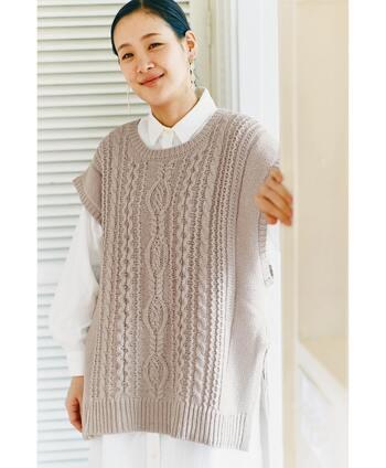 綿100%の糸でふっくらと仕上げた、模様編みの二ットベストです。大人っぽいグレージュカラーは、ナチュラルな着こなしにもぴったり。サイドに付いたリボンが着こなしのアクセントになってくれます。