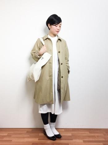 白のシャツワンピースにステンカラーコートを羽織った、クラシックな着こなし。レギンスと黒のバレエシューズの境界線をはっきりするように白ソックスを間に挟む一手間が、コーディネートにメリハリを加えます。