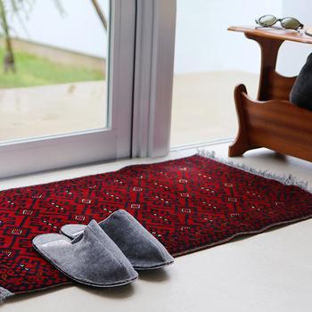 エスニックなムード漂う中東で作られた手織絨毯、「トライバルラグ」。小さめサイズなので、玄関マット、ソファーの下やスツールやキャビネットの下など、いろんなシーンで使えて重宝します。しっかり重みがあって丈夫なので、ほとんどズレを気にせず使えるのも嬉しい。筆者はリビングのソファ横に設置。木の置物や観葉植物を上に置いて使っています。