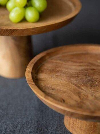 木製の雑貨は一見簡素なようだけど、フォルムや木目の美しさが際立ち、有機的な表情も魅力的です。チークウッドの脚付きプレートは、秋の果物や木の実が映える佇まい。ダイニングテーブルやキッチンカウンターはもちろん、飾り棚において雑貨やアクセサリーを並べるのも素敵です。