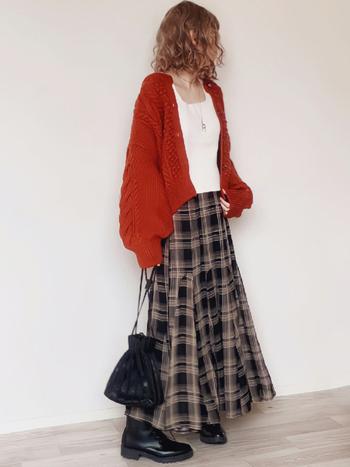 ダークカラーのチェックのスカートには、トレンドカラーのオレンジのカーデを合わせて。シンプルなカットソーにメタリックなネックレスが映えます。