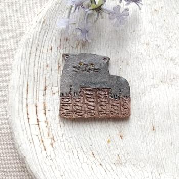 黒猫さんが板チョコの上に乗っている構図がちょっぴりシュールなのに可愛い、焼き物のブローチ。土の雰囲気を生かす成型や色付けで、ナチュラルなファッションのポイントになりそう。