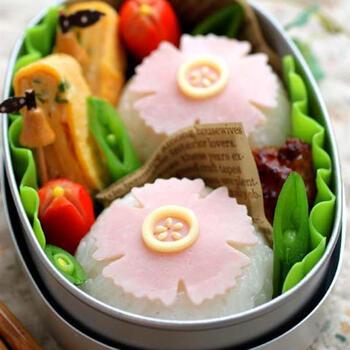 おにぎりの上に花の形に抜いたハムをのせるだけでこんなに華やかに。チーズと白ごまで中心を飾れば、よりリアルな花を表現できますよ。