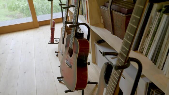 本棚の前には、音楽スペースも。ギターやドラムなどの楽器もしまわずにスタンドを使って飾られています。
