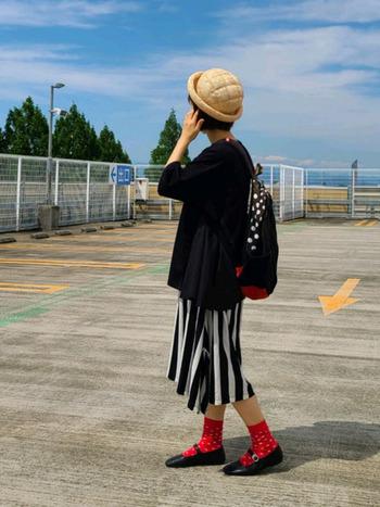 スカートに大きめの縞々、リュックに水玉を忍ばせたアートな雰囲気満点のコーデ。全体は黒ベースだけど、靴下に赤を取り入れたり、ドットやストライプなどのスパイスを随所に効かせた個性が光るスタイリングです。