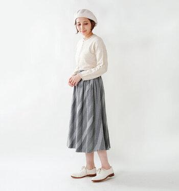 白とグレーの2色で統一された、ノーブルなスタイル。斜めストライプの温かみあるスカートを1点投入するだけで、マンネリになりがちなコーデが一気にブラッシュアップされます。