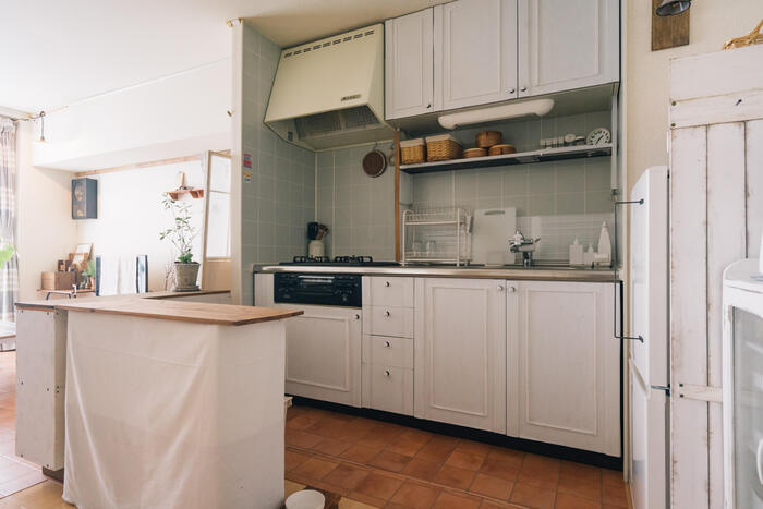 木製の収納部分を持つキッチンとペールカラーのタイルがシンプルにカントリー。DIYされた収納扉はモールディング風の飾りがポイントになっていて素敵です。左の白いカラーボックスはやすりがけで塗料を程よく剥がしたそう。賃貸ながらも様々な工夫で統一された空間になっています。