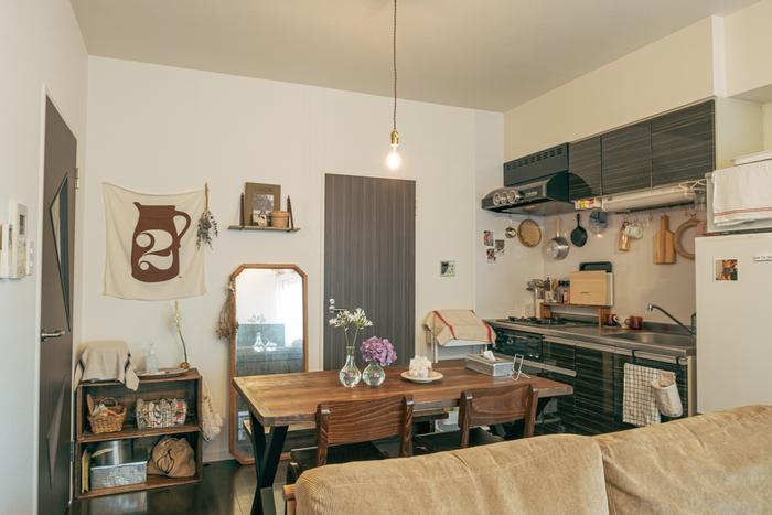 キッチンはモダンですが、木目のような模様が存在感のあるダイニングセットと調和し、全体的にはカントリーな雰囲気になっています。左端にあるりんご箱をDIYした棚も、ダークな色味で味わい深いですね。