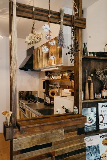 ダークな木材でDIYされたカウンターやドライフラワー、収納扉の木材風リメイクシートが自然の素材感たっぷりなキッチン。どちらかというとカフェ風なカントリースタイルになっています。