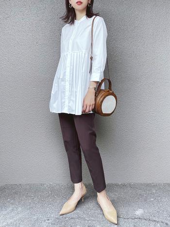 裾のプリーツが印象的な白のブラウスを、こっくりブラウンのパンツで秋冬らしい着こなしへ誘導。ヌーディーなポインテッドトゥのパンプスでメリハリを効かせつつ、素肌がボトムの重厚感を適度に抑制してバランスを整えます。