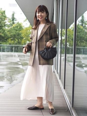 プリーツの切り替えなどリズムのある白のワンピースに、ジャケットを羽織ってお仕事スタイルへ転換。チェックなら適度に遊び心も加えられ、ワンピースの甘さもうまく引き立ちフェミニンな着こなしに着地します。