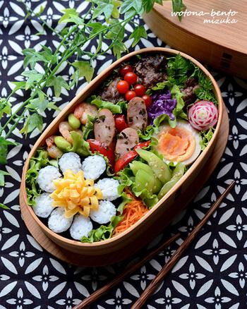 """海苔を巻き切らずに作るしずく型の海苔巻き、""""海苔巻かず""""を花びらに見立てて。たまごの飾り切りをのせれば本物の花みたい!お米はおしゃれに減らして、おかずはたっぷりなヘルシー弁当です♪"""