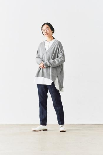 テーパードジーンズに、ゆったりシルエットのトップスでバランスよく着こなしたコーディネートです。グレーの深めVネックに、白のブラウスをレイヤードしたナチュラルな印象の着こなし。足元も白のシューズで、デニムスタイルを大人っぽく仕上げています。