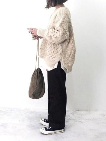 オーバーサイズのざっくりニットを着る場合は、重ね着で立体感を演出するとGOOD。サイドスリットのデザインは脚長効果も抜群です。パンツとスニーカーを黒で揃え、グッと大人っぽいコーデに。