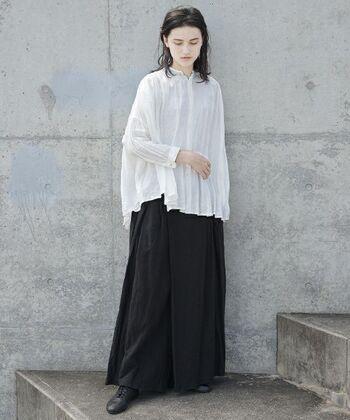 ふんわりブラウスと、巻きスカートのような大胆なデザインのワイドパンツ。可愛らしくなりがちな組み合わせでも、白と黒のモノトーンでまとめることで、落ち着いた大人のスタイルに。