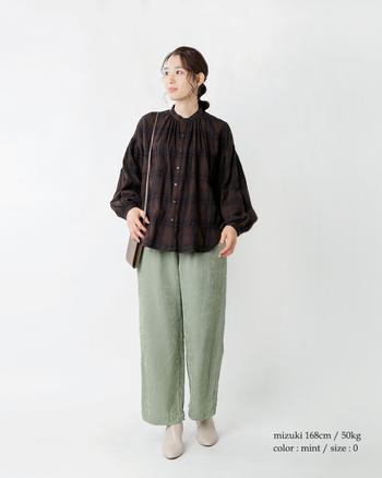 柔らか素材で光沢感のあるパンツは、カジュアルにもエレガントにも使える万能アイテム。ブラウン系のシャツを合わせて軽やかなコーデに。